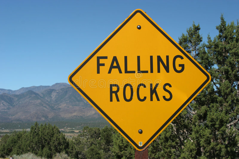 Falling rocks ahead road sign. Falling rocks road sign and scenery stock photography