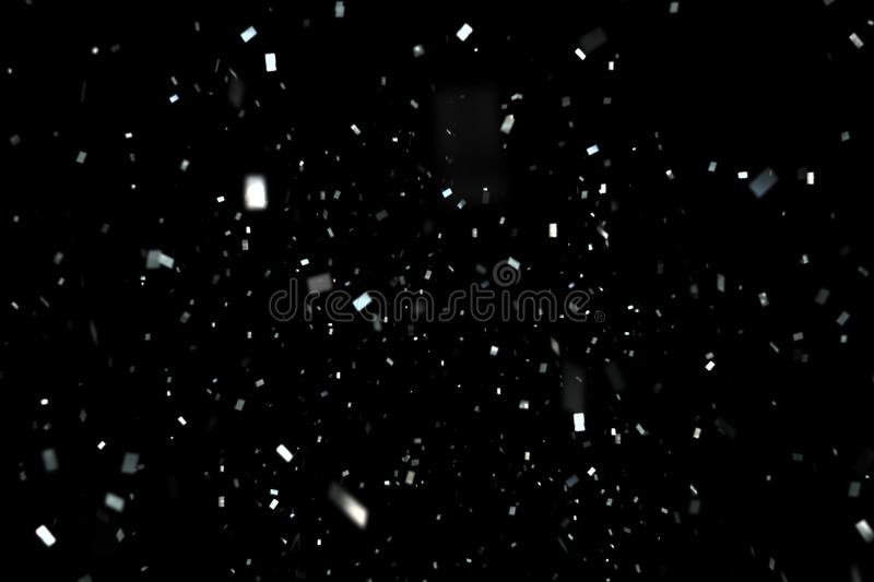 Falling silver metallic glitter foil confetti, animation movement on black background, holiday and festive fun. Concept royalty free stock photography