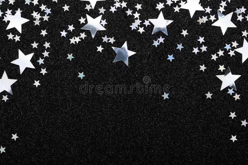 Falling silver stars confetti on black festive background Glowing sparkles frame. Falling silver stars confetti on black Festive holiday background. Glowing stock photography