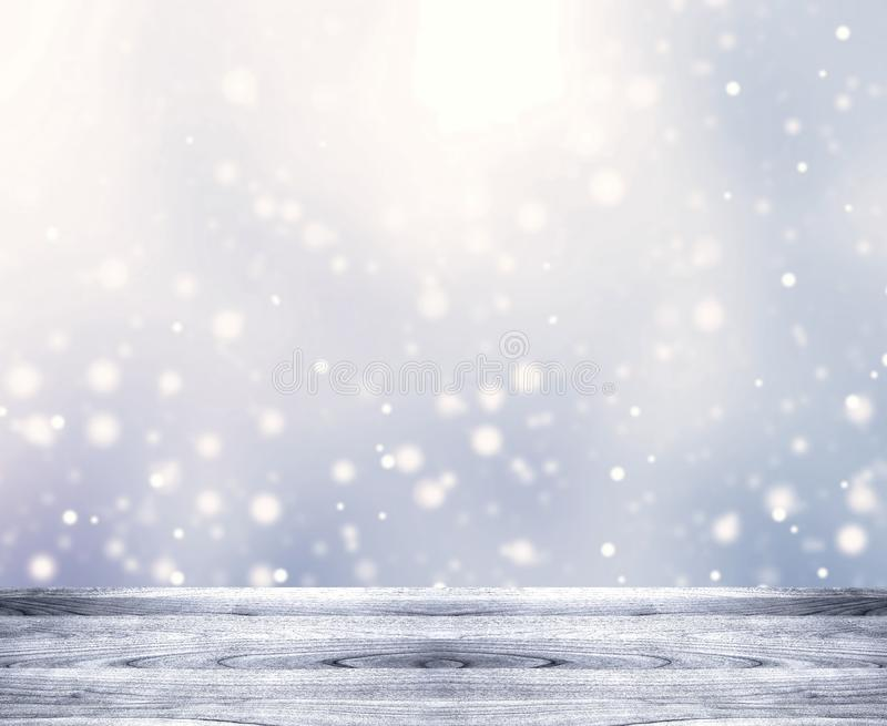 Falling snow. Light rustic wooden empty table. Winter blurred background. Gentle New year background. stock photos