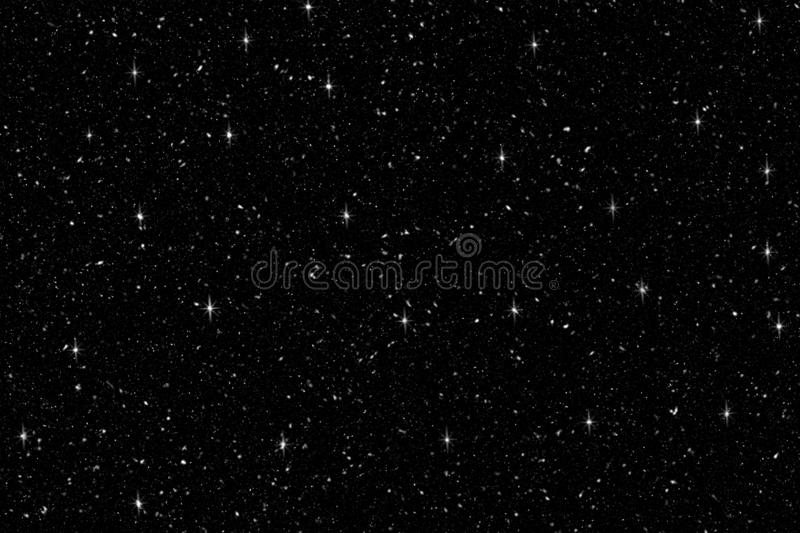 Falling snow with shine glitter on black background. Winter background in pure dark. Heavy snow. royalty free stock photo