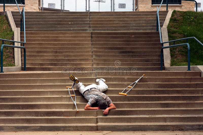 Falling on stairs. Man laying on stairs after falling with crutches by his side stock images