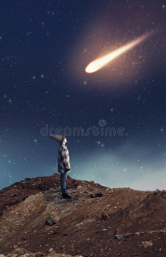 Falling star kid. Kid looking up to a falling star during the night stock images