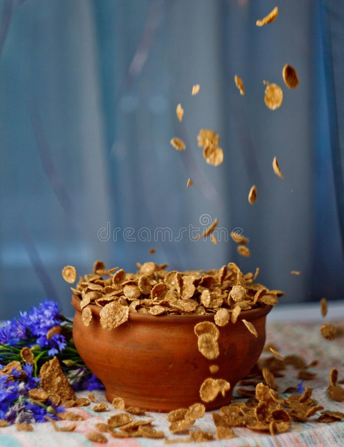 Falling sugar cornflakes in a ceramic bowl close-up top view. light breakfast scattered on the table with blue flowers close-up stock images