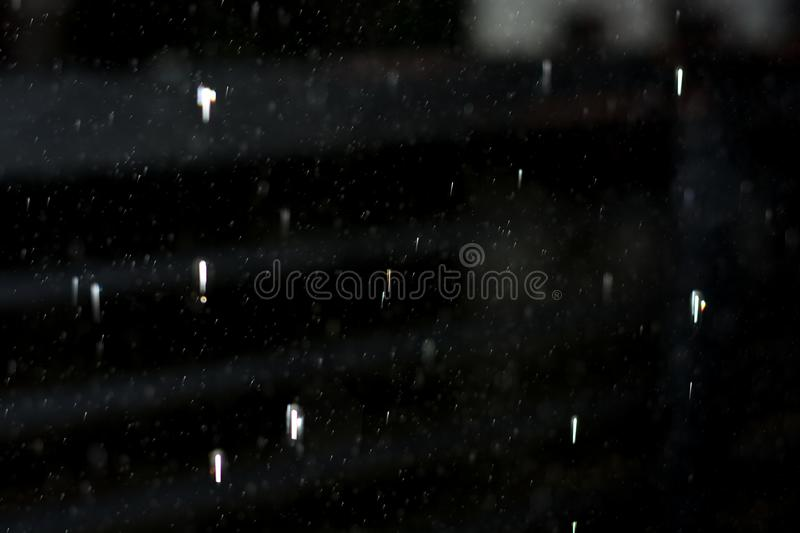 Falling water droplets in black background. Drops of rain water falling at night with flash and white reflection stock images