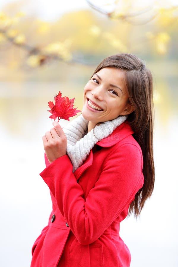 Fallmädchen, das draußen roten Herbsturlaub hält lizenzfreies stockbild