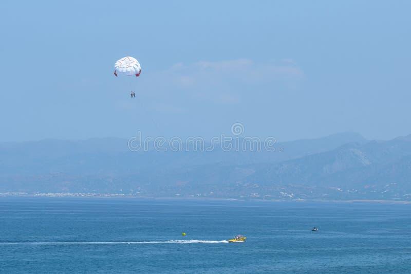 Fallschirmspringen über ein Meer, schleppend durch ein Boot Fahren auf einen Fallschirm stockbilder