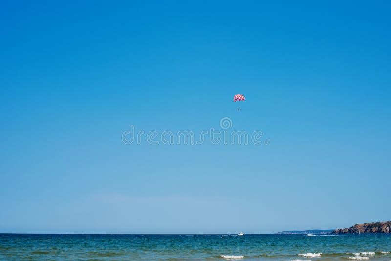 Fallschirmspringen über ein Meer, schleppend durch ein Boot Gleitschirmfliegen im klaren Himmel über dem Meer Fahren auf einen Fa lizenzfreie stockbilder