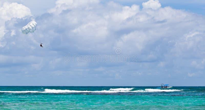 Fallschirmspringen in das karibische Meer lizenzfreie stockbilder