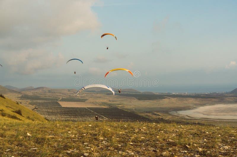 Fallschirmspringer, die im blauen Himmel über szenischer Landschaft von Krim gleiten, Ukraine, stockfotografie