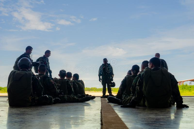 Fallschirmteamleiter unterweist seine voller Gang ausgerüsteten Truppen im Flugzeughangar lizenzfreie stockfotos
