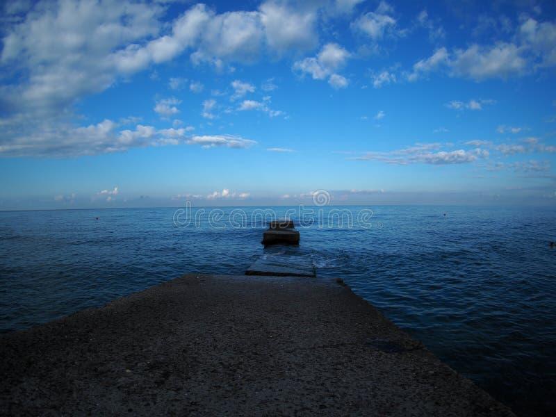 Falochron ciie przez spokojnego morze prawie horyzont zdjęcie stock