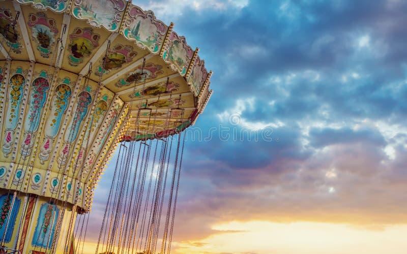 Falowa hulaki corousel przejażdżka przeciw niebieskiemu niebu, rocznika filtrowy effe zdjęcie stock