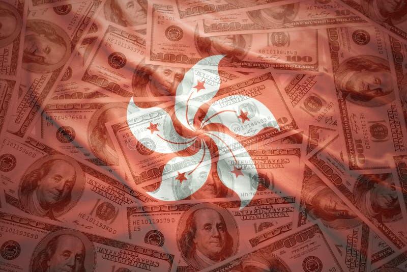 falowania Hong kong flaga na amerykańskim dolarowym pieniądze tle zdjęcia stock