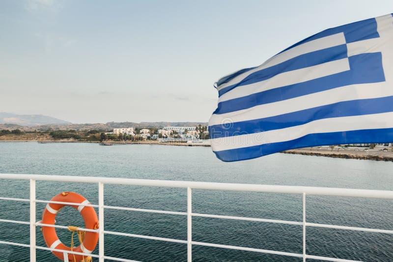 Falowanie grka flaga i pomarańczowy lifebuoy obwieszenie na białego metalu zbawczym poręczu przy Kos wyspą przeglądamy tło fotografia stock
