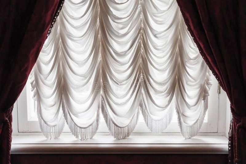Falowanie tiul i zmrok - czerwona zasłona na okno obraz royalty free