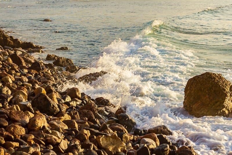 Falowy łamanie na skalistym brzeg wygina się w odległość obrazy stock