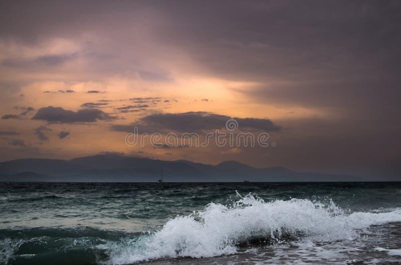Falowy miażdżenie plaża podczas kolorowego zmierzchu fotografia stock