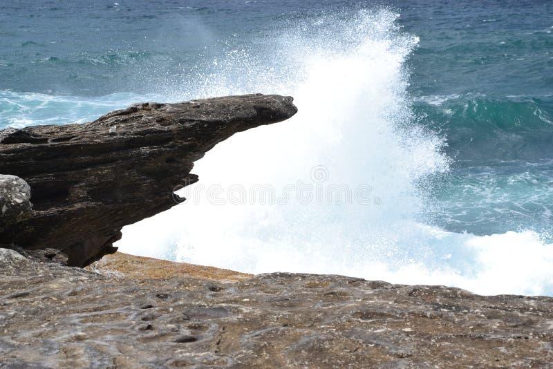 Falowy rozbijać przeciw skałom obrazy stock