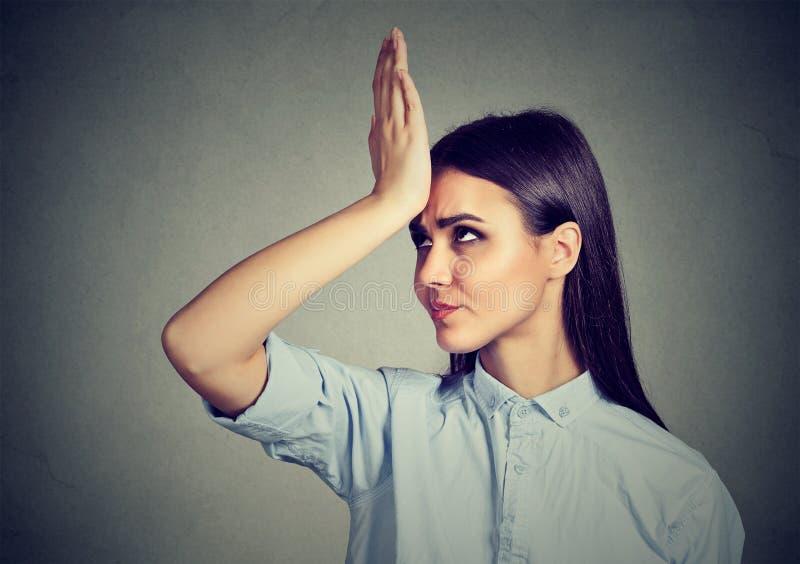 Falsches Handeln Umgekippte Frau des Nahaufnahmeporträts, Hand auf dem Kopf schlagend, der duh Moment hat stockfotos