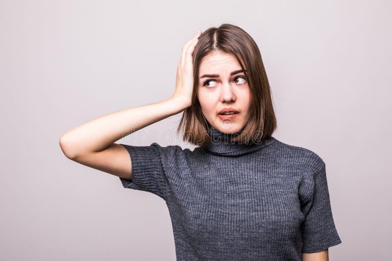 Falsches Handeln Umgekippte Frau des Porträts, Hand auf dem Kopf schlagend, der duh Moment auf grauem Hintergrund hat stockfotos