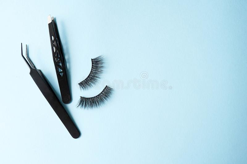 False eye lashes, black tweezers on blue background with copy space, mockup. Instruments: Beauty and fashion concept - Tools for stock photo
