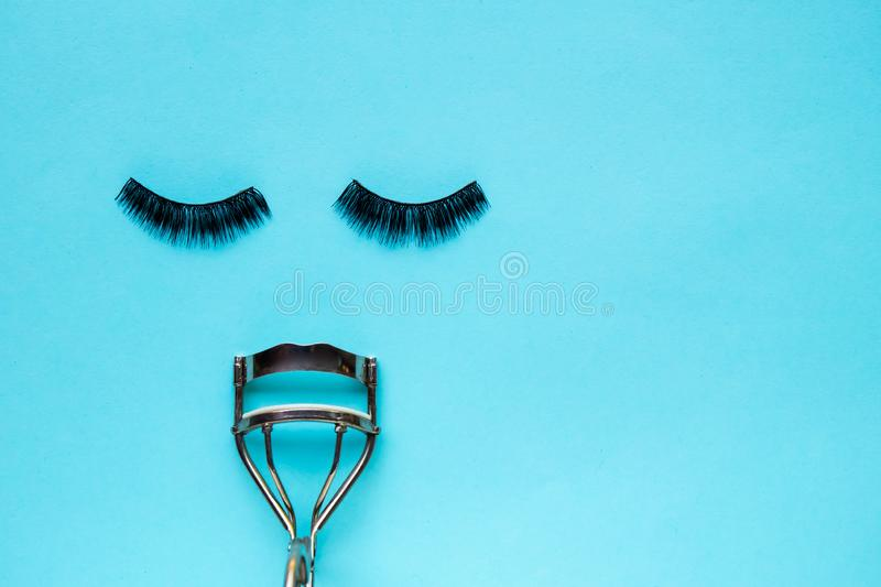 False Eyelashes and eyelash curler. On blue background adhesive artificial beautiful beauty black care close closeup colorful concept copy space cosmetic stock photography
