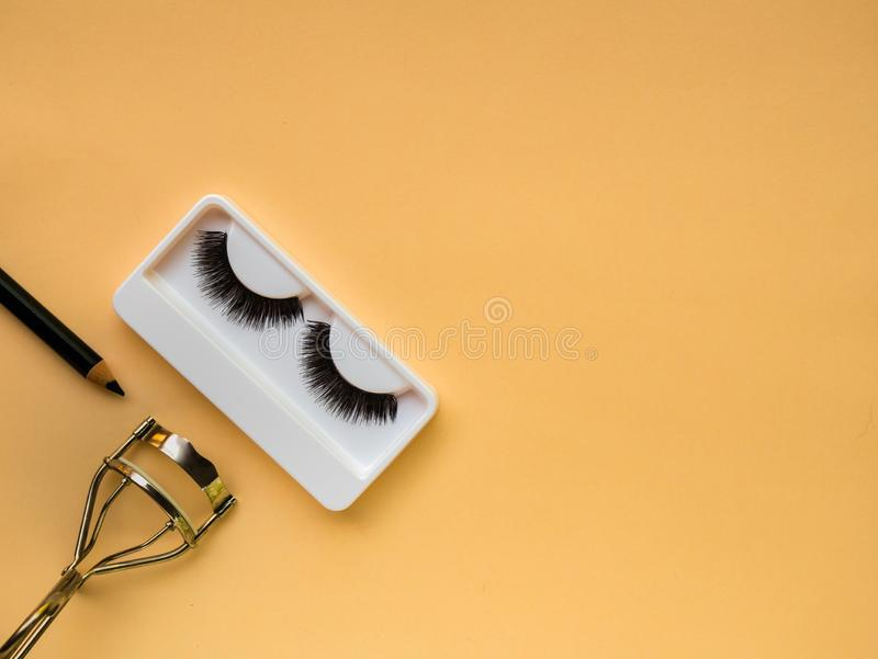 False Eyelashes, eyelash curler and eye liner. On yellow background adhesive artificial beautiful beauty black care close closeup colorful concept conceptual stock photography