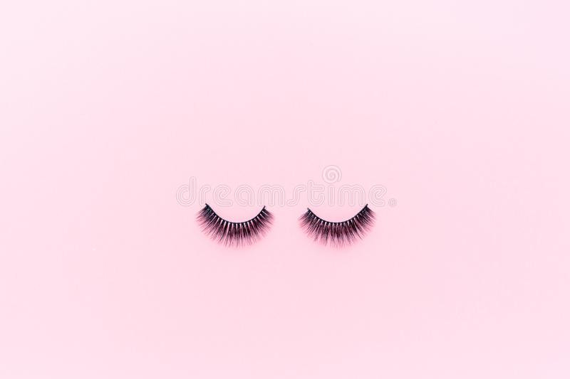 False eyelashes lying on pink background. Beauty and makeup concept. Flatlay, mockup, overhead, top view copy space stock photo