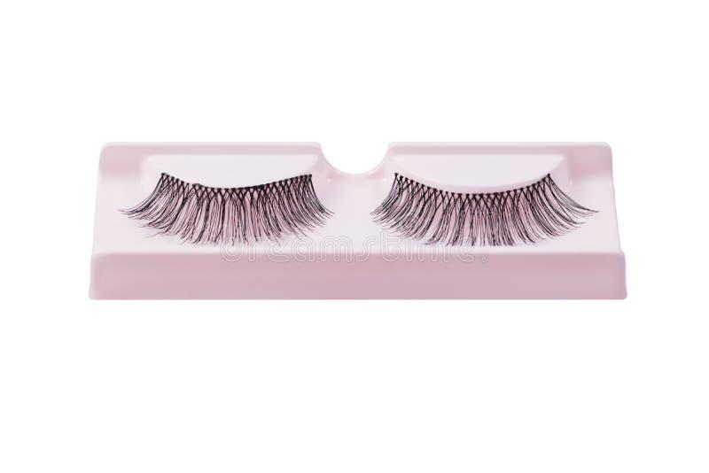 False eyelashes pair on pink display isolated on white royalty free stock images