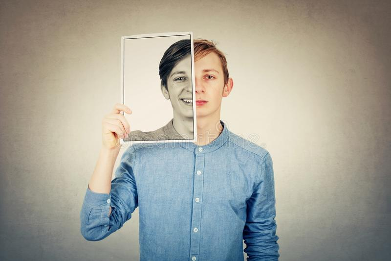 False portrait of a sad boy teenager hiding half face using a photo print paper sheet with a fake happy emotion. Mask for hiding royalty free stock photography