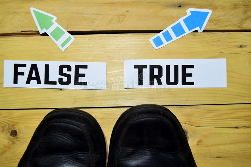 False or True opposite direction signs with Boots on wooden vintage background. Business, education and finance concepts stock photos
