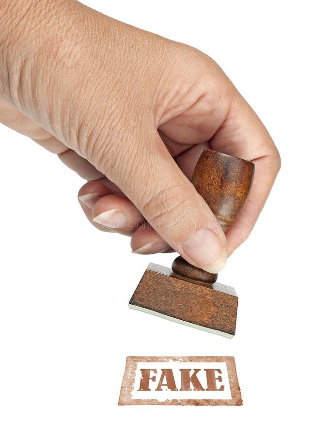 Falsificación auténtica, sello de goma Mi mano con el sello de goma aislado en blanco Concepto ético del negocio, de la política  foto de archivo libre de regalías
