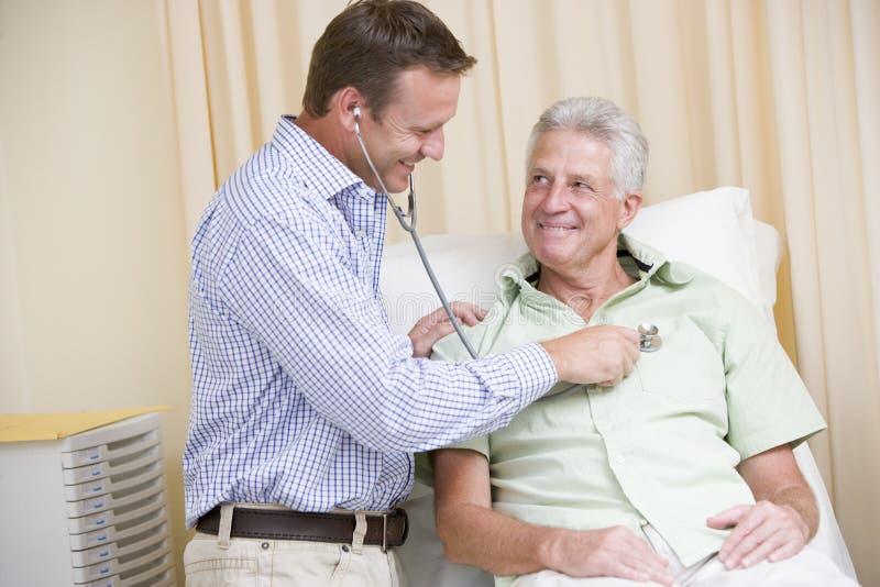 Falsifichi dare il controllo dell'uomo con lo stetoscopio nell'esame immagine stock libera da diritti