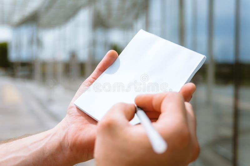 Falsk övre anteckningsbok i en mans hand, mot bakgrunden av en exponeringsglasbyggnad royaltyfri fotografi
