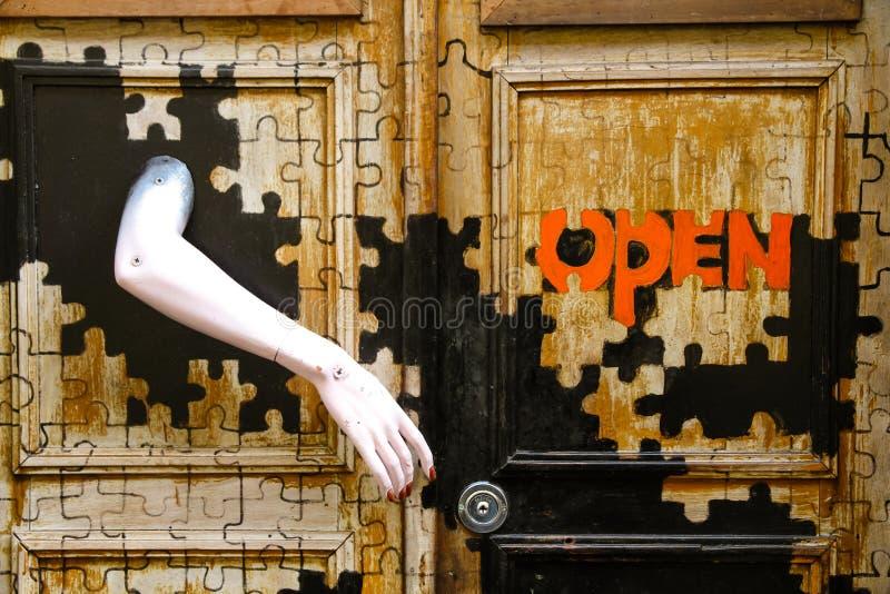 """Falsk kvinnlig arm för overklig för dörr röd skyltdocka för text öppen, som handtaget på ett pussel målade ingången i """"Thekonst royaltyfria foton"""