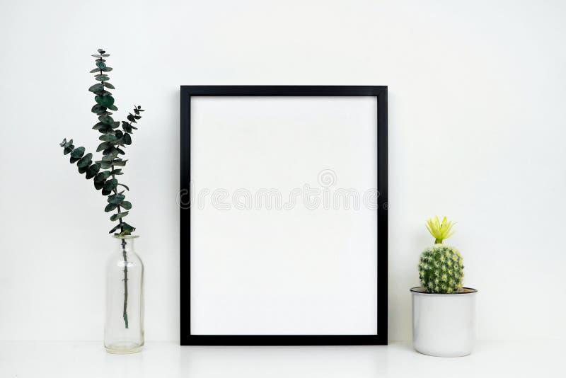 Falsk upp svart ram med kaktuns och filialer på en vit hylla eller skrivbord mot en vit vägg royaltyfria bilder