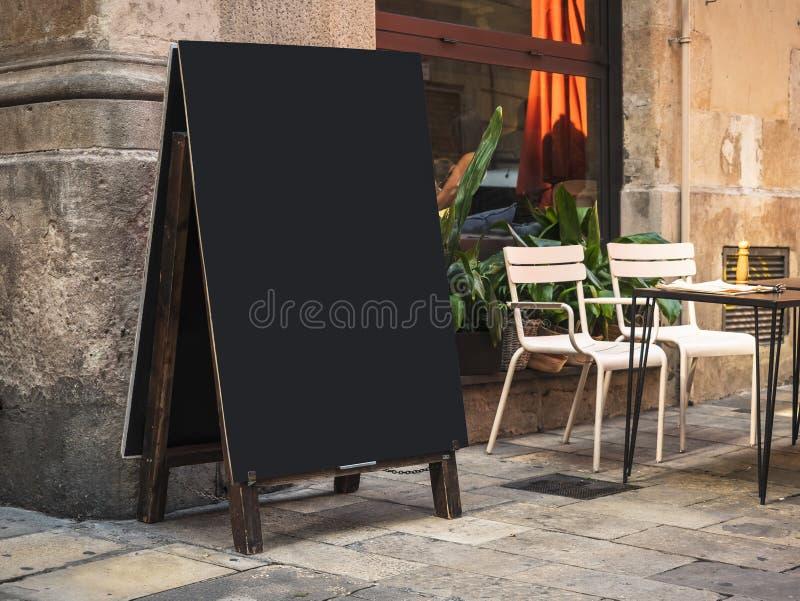 Falskt övre kafé för gata för restaurang för svart tavla för menyskyltmellanrum med tabellplatser arkivbild