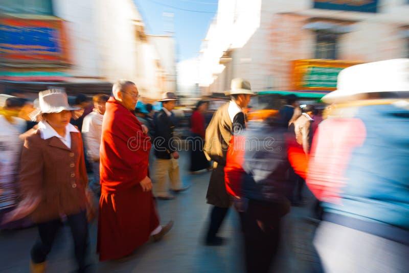 Falta de definición de Barkhor Jokhang de los peregrinos que camina tibetanos imagenes de archivo