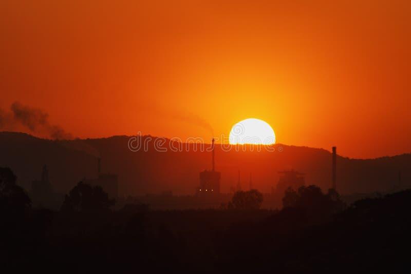 Falta de definición, fábrica industrial en imagen de la silueta en la puesta del sol imágenes de archivo libres de regalías