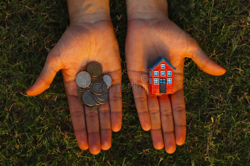 Falta de dinero para comprar un concepto de la casa El hombre sostiene la casa del juguete en un mano y puñado de monedas en otro imagenes de archivo