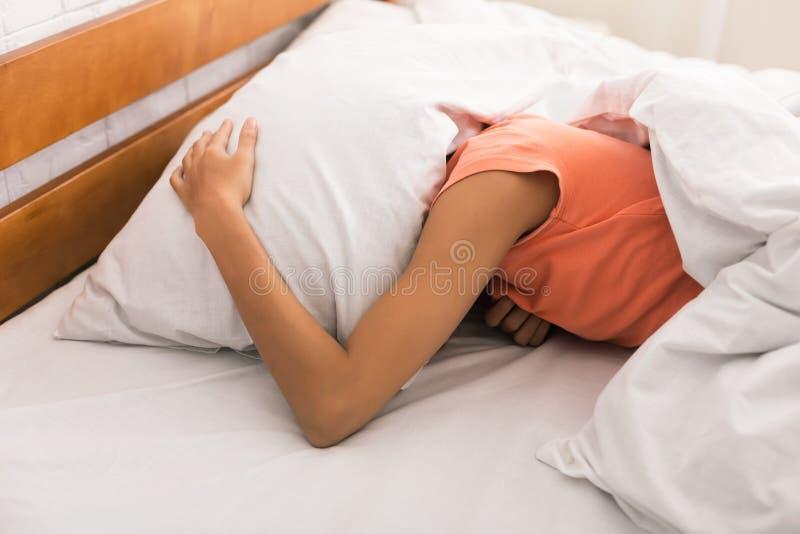 Falta do sono Cabeça da coberta da mulher com descanso foto de stock