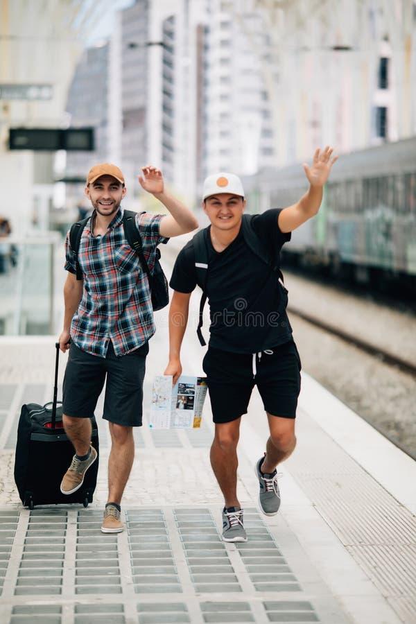 Falta do viajante de dois homens ou atrasado no trem e no corredor após o trem na plataforma na estação de trem conceito do curso imagem de stock royalty free