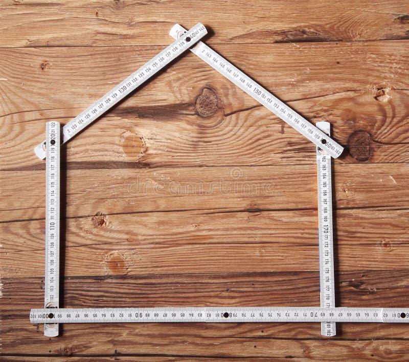 Falten-Machthaber, der ein Haus auf Holztisch bildet lizenzfreie stockfotos