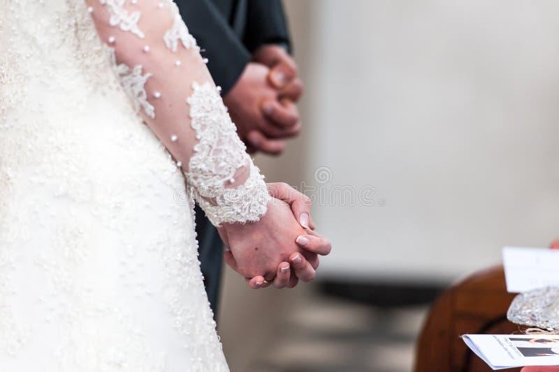 Faltende Hände der Braut und des Bräutigams in der Kirche lizenzfreie stockbilder