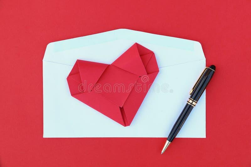 faltendes rotes Papierherz auf weißem Umschlag und schwarzem Geschäftsstift lizenzfreies stockbild
