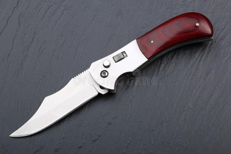 Faltendes Stahlmesser mit einem offenen Blatt und einem Holzgriff auf einer Steinoberfläche Stahlarme Das Konzept der Waffe, der  stockfotos