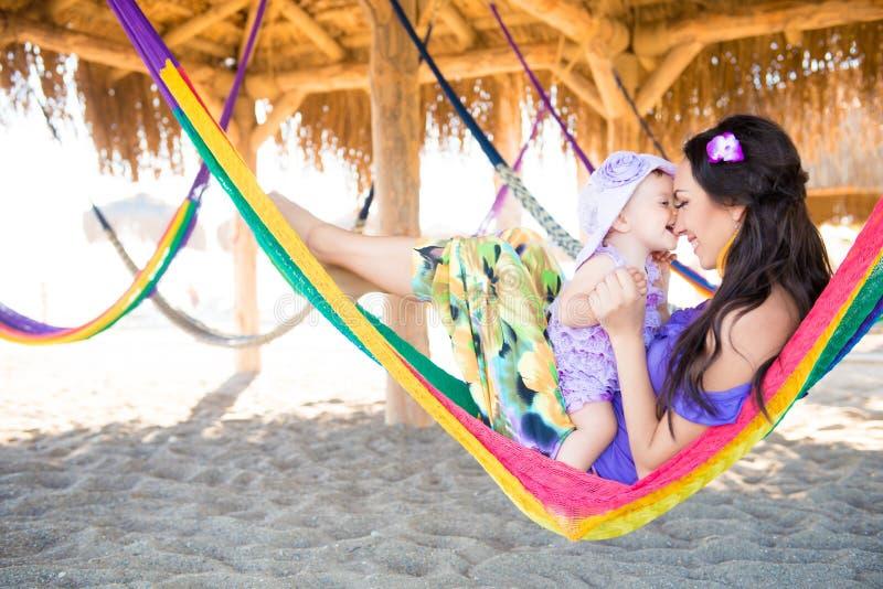 Família à moda feliz com a filha bonito que relaxa na rede em férias de verão na luz do sol da noite na praia pares w do moderno imagens de stock royalty free