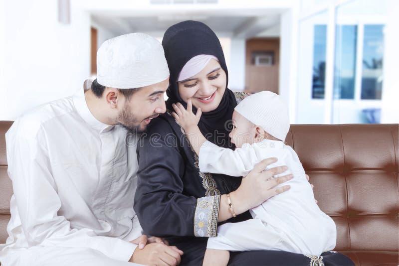 Família árabe alegre que graceja em casa imagem de stock