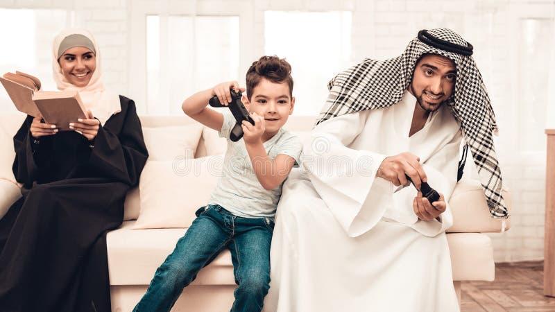 Família árabe feliz que joga no console em casa imagens de stock royalty free